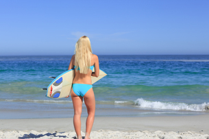 Beautiful blonde woman with her surfboardの写真素材 [FYI00484088]