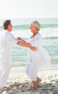 Elderly couple dancing on the beachの写真素材 [FYI00484092]