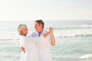 Elderly couple dancing on the beachの写真素材 [FYI00484095]