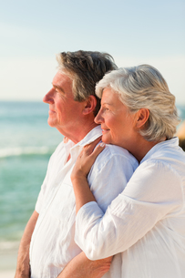 Woman hugging her husband at the beachの写真素材 [FYI00484096]