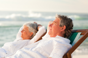 Elderly couple relaxing in their deck chairsの素材 [FYI00484098]