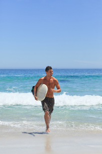 Man running on the beach with his surfboardの写真素材 [FYI00484117]
