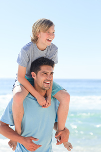 Father having his son a piggyback at the beachの写真素材 [FYI00484119]