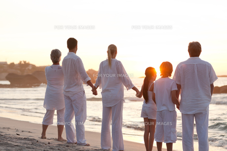 Family at the beach during the sunsetの写真素材 [FYI00484136]