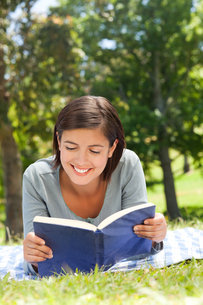 Woman reading a book in the parkの写真素材 [FYI00484139]