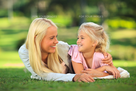 Mother with her daughter lying down in the parkの写真素材 [FYI00484162]