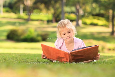Little girl looking at her album photoの写真素材 [FYI00484163]