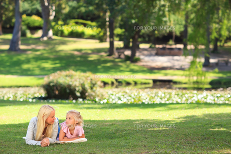 Mother with her daughter lying down in the parkの写真素材 [FYI00484164]