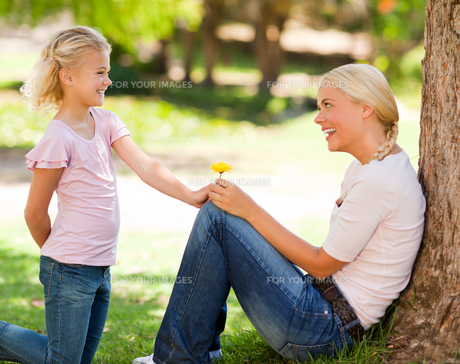 Daughter offering a flower to her motherの写真素材 [FYI00484168]