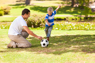Father playing football with his son in a parkの素材 [FYI00484173]