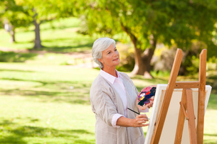 Senior woman painting in the parkの写真素材 [FYI00484186]