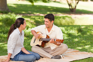 Romantic man playing guitar for his wifeの写真素材 [FYI00484205]
