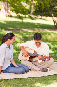 Romantic man playing guitar for his wifeの写真素材 [FYI00484208]