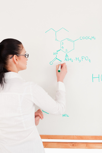 Scientist writing a formula on a whiteboardの写真素材 [FYI00484219]