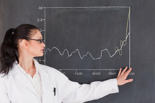 Female scientist showing a graph on the blackboardの写真素材 [FYI00484224]