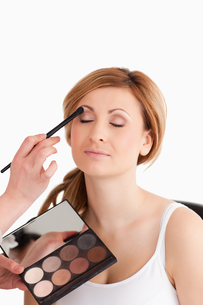 Makeup artist applying make up to a young woman in a studioの写真素材 [FYI00484226]