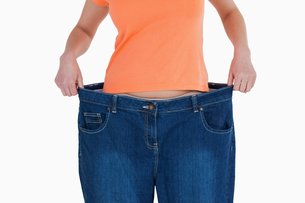 Slim woman showing how much weight she lostの写真素材 [FYI00484254]
