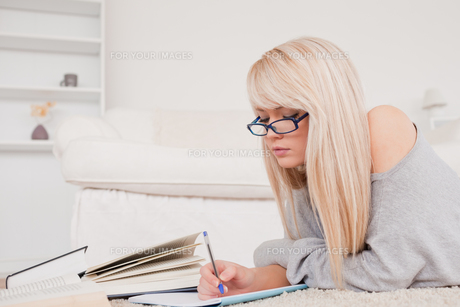 Concentrated blonde woman studying while lying on a carpetの素材 [FYI00484255]
