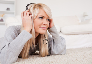 Beautiful blond woman with headphones lying on a carpetの素材 [FYI00484257]