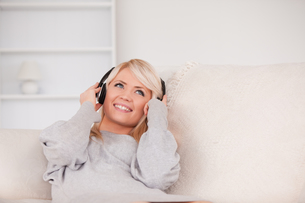 Attractive blond woman with headphones lying in a sofaの素材 [FYI00484264]