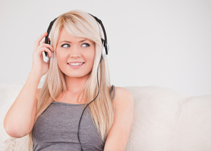 Beautiful young blond woman with headphones sitting in a sofaの写真素材 [FYI00484265]