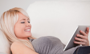 Attractive woman lying on a sofa relaxing on a line of tablet computersの写真素材 [FYI00484266]