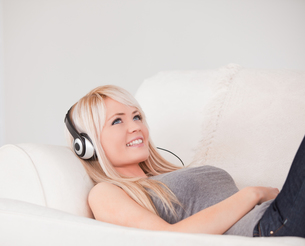 Happy young blond woman with headphones lying in a sofaの素材 [FYI00484267]