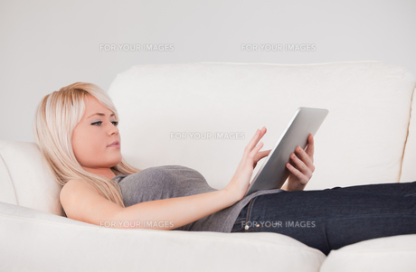 Pretty woman lying on a sofa relaxing on a line of tablet computersの写真素材 [FYI00484269]