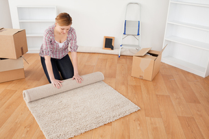Cute woman rolling up a carpet to prepare to move houseの素材 [FYI00484270]