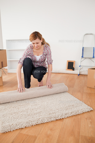 Pretty woman rolling up a carpet to prepare to move houseの素材 [FYI00484272]
