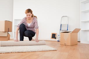 Lovely woman rolling up a carpet to prepare to move houseの素材 [FYI00484273]