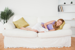 Attractive woman taking a rest while lying on a sofaの写真素材 [FYI00484287]