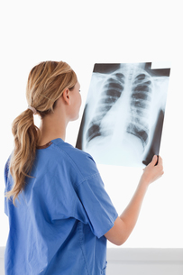 Cute female doctor looking at an Xrayの写真素材 [FYI00484288]