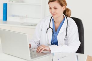 Attractive female doctor working on her laptopの写真素材 [FYI00484289]