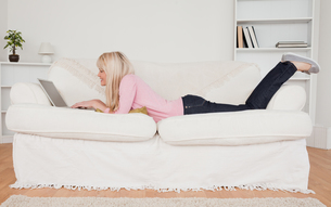 Young smiling woman relaxing with a laptop while lying on a sofaの素材 [FYI00484290]