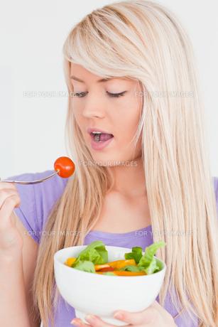 Beautiful smiling woman eating her saladの素材 [FYI00484298]