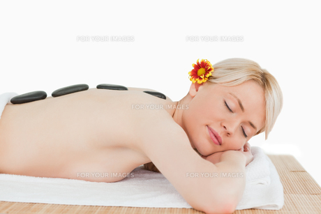 Cute blonde woman relaxing with hot stones on her backの写真素材 [FYI00484299]