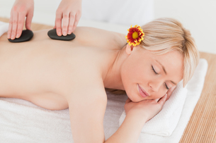 Delighted blonde woman receiving a massage with hot stones in a Spa centreの写真素材 [FYI00484301]