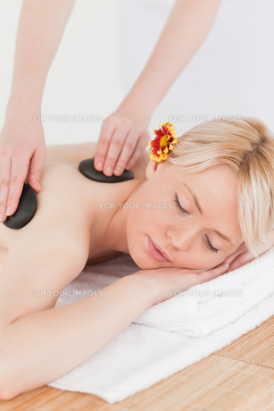 Beautiful woman receiving a massage with hot stonesの素材 [FYI00484302]