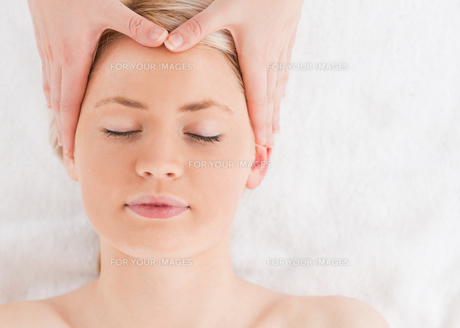 Delighted young woman getting a massage on her faceの写真素材 [FYI00484310]