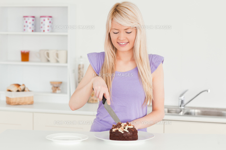 Smiling blonde female cutting a cake in a plateの写真素材 [FYI00484311]