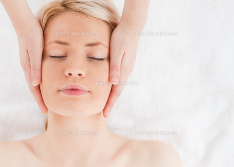 Delighted blondhaired woman getting a massage on her faceの写真素材 [FYI00484312]