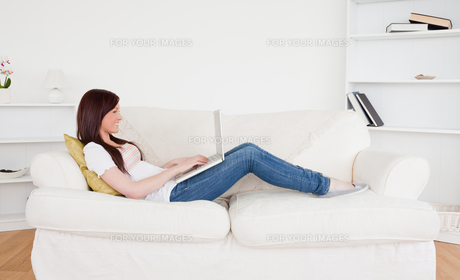 Beautiful redhaired female relaxing with her laptop while lying on a sofaの写真素材 [FYI00484313]