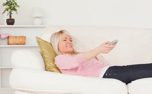 Good looking blonde female watching tv while lying on a sofaの写真素材 [FYI00484314]