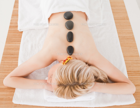 Young blonde woman relaxing with hot stones on her backの素材 [FYI00484315]