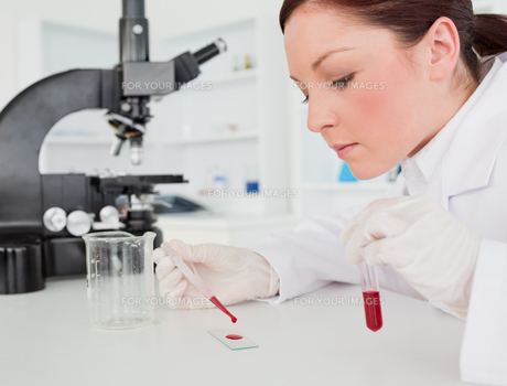Cute redhaired female scientist doing an experiment in a labの素材 [FYI00484327]