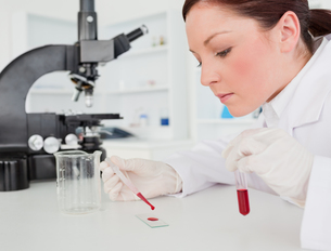 Cute redhaired female scientist doing an experiment in a labの写真素材 [FYI00484327]