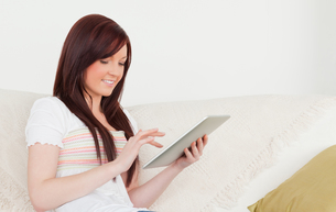 Good looking redhaired woman relaxing with her tablet while sitting on a sofaの写真素材 [FYI00484328]