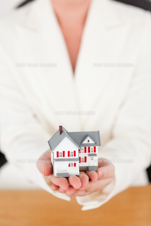 Young pretty redhaired female in suit holding a miniature houseの素材 [FYI00484332]