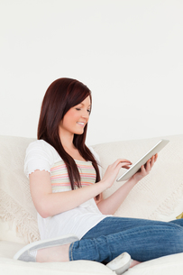 Beautiful redhaired woman relaxing with her tablet while sitting on a sofaの素材 [FYI00484333]